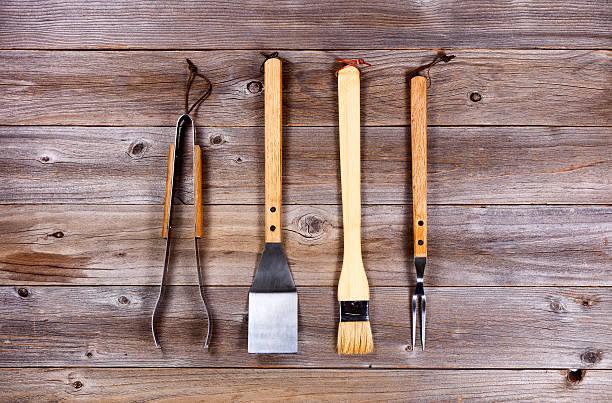 used kitchenware for barbecue cooking on rustic wood - keukengereedschap stockfoto's en -beelden