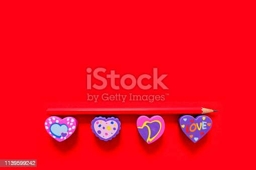 istock Used Love Pink and Purple Eraser Symbol for Valentine Day Concept. Education Toy Top View. Colorful Heart Erasers and Red Pencil Isolated on Red Paper Color Background with Banner, Clean Copy Space. 1139599242