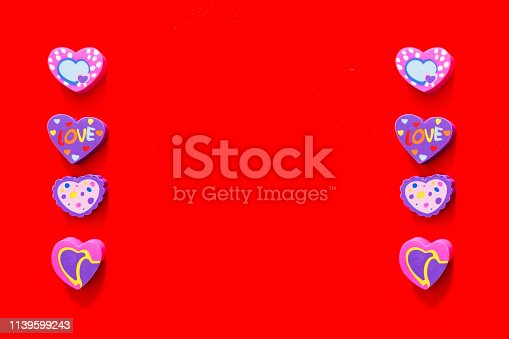 istock Used Love Pink and Purple Eraser Symbol for Valentine Day Concept. Education Card for School. Colorful Heart Erasers Toys Top View Isolated on Red Paper Color Background with Banner, Clean Copy Space. 1139599243