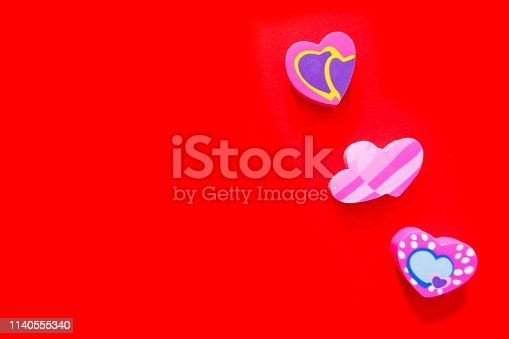istock Used Love Pink and Purple Eraser Symbol for Valentine Day Concept. Education Card for School. Colorful Heart Erasers Toys Top View Isolated on Red Paper Color Background with Banner, Clean Copy Space. 1140555340