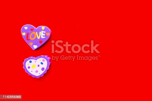 istock Used Love Pink and Purple Eraser Symbol for Valentine Day Concept. Education Card for School. Colorful Heart Erasers Toys Top View Isolated on Red Paper Color Background with Banner, Clean Copy Space. 1140555365