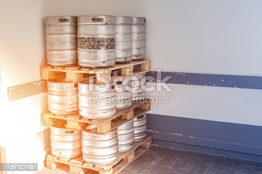 istock Used metal beer keg barrel on wooden pallets in corner of warehouse after delivery. Steel drink containers storage 1157121187
