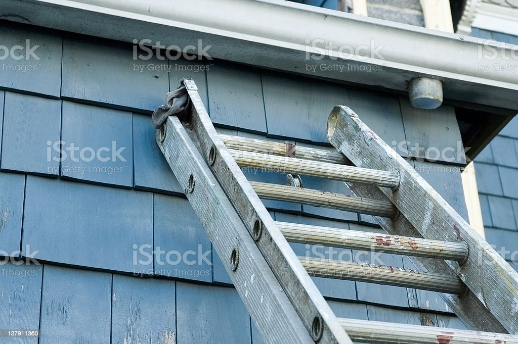 Used metal ladder placed upon a house stock photo