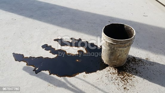 1001622522 istock photo Used oil spill is on the floor. 967547780