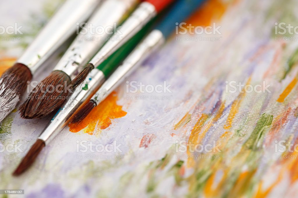 Used paint brushes on a painted canvas stock photo