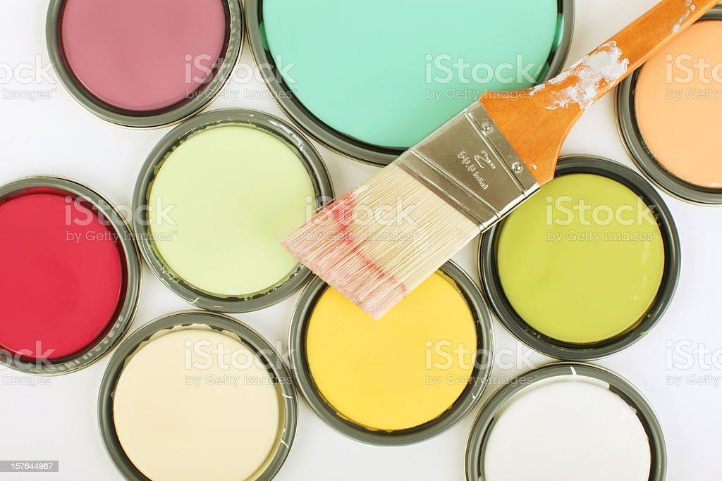 Used paintbrush on top of paint can lids royalty-free stock photo