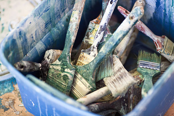 Used Paintbrushes in a Plastic Bin stock photo