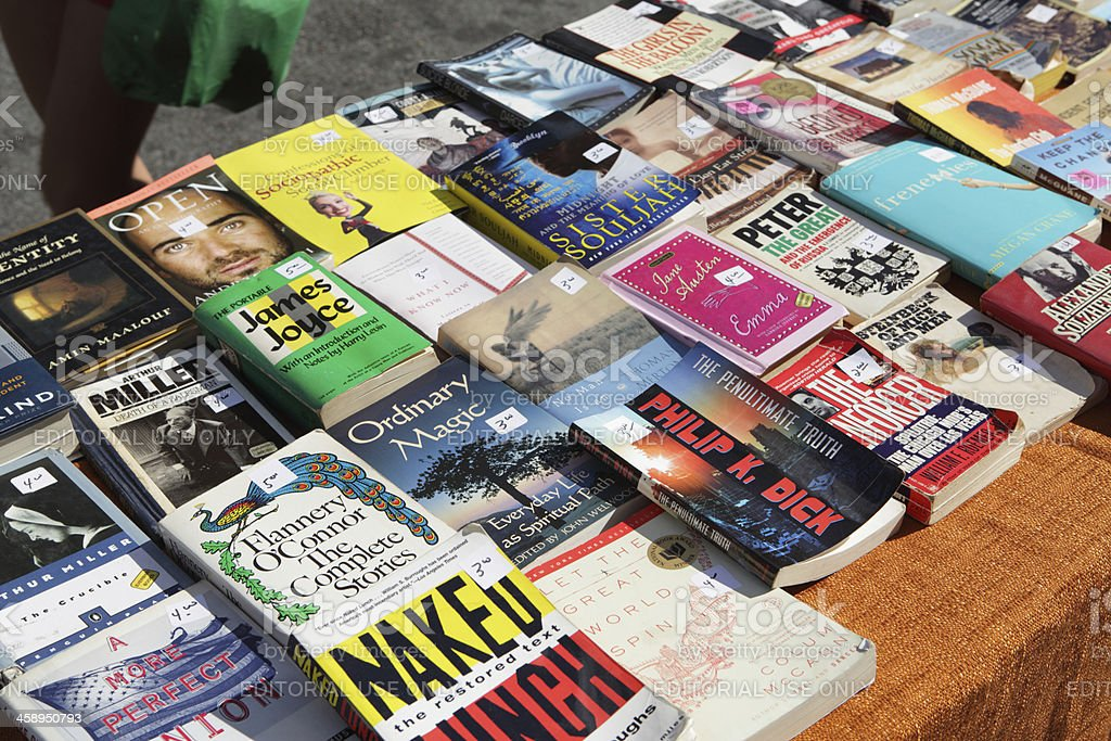 Used paperback books for sale on street vendor stand stock photo