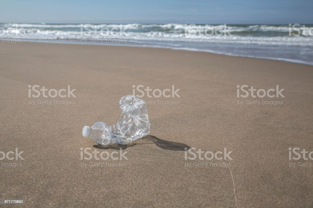 A used plastic bottle is lying on the beach stock photo