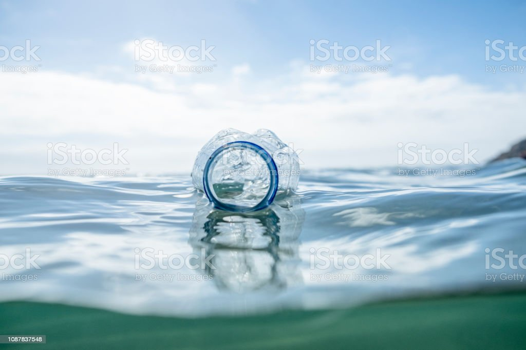 Used Plastic Water Bottle floating on the sea surface. stock photo