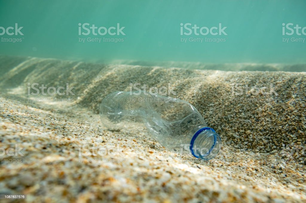 Used Plastic water bottle on the seabed. stock photo