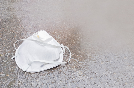 Used Protective Mask On The Ground - Fotografie stock e altre immagini di Abbandonato
