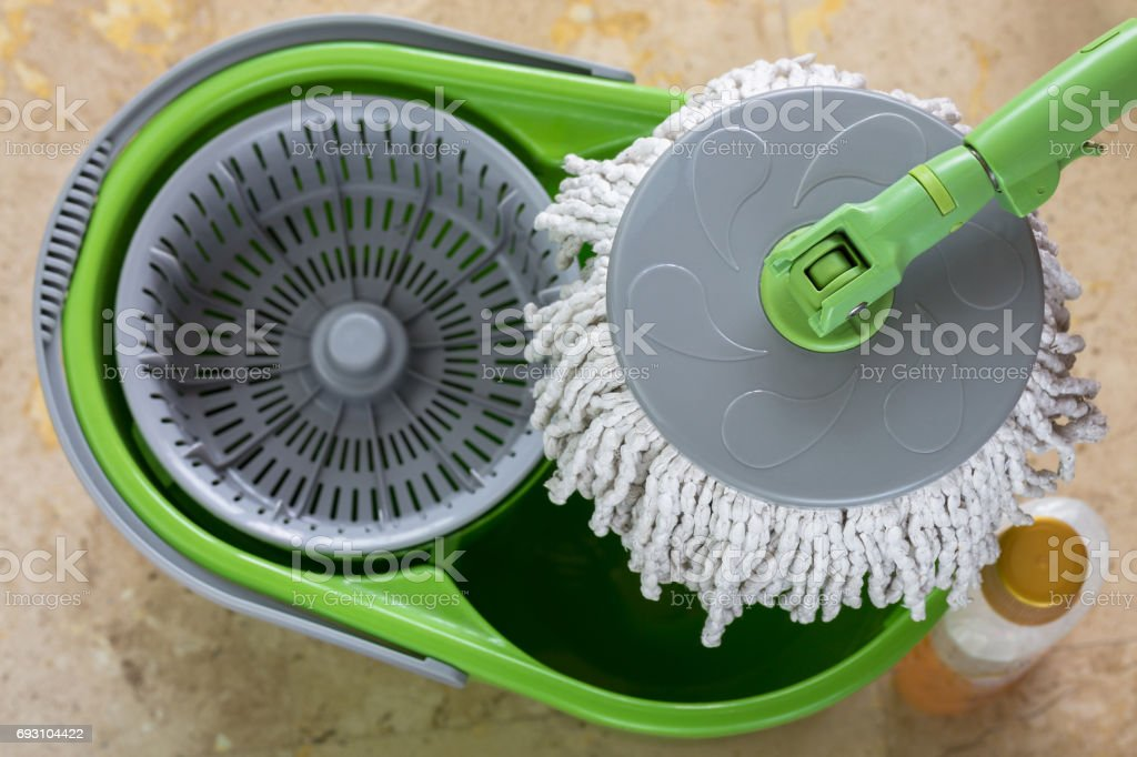 Used round spin mop with microfiber head, green handle on cleaning bucket next to floor cleaning liquid stock photo