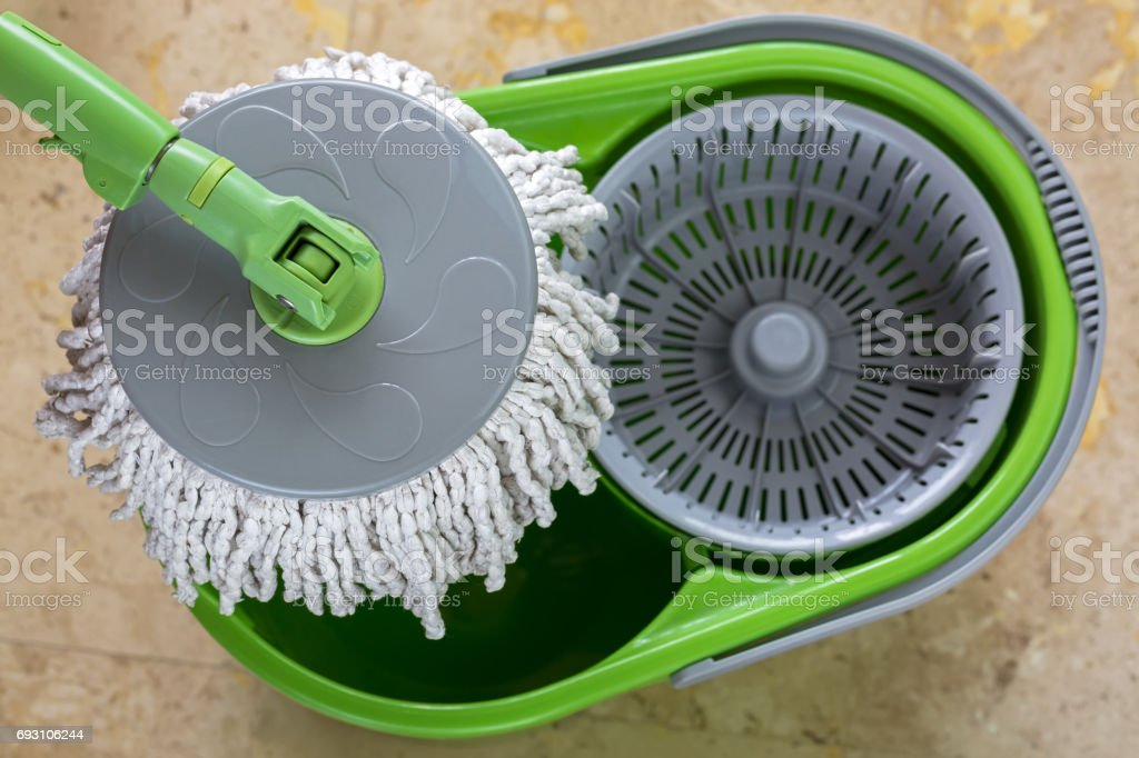 Used round spin mop with microfiber head, green handle on cleaning bucket stock photo