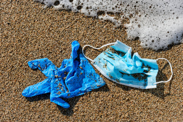 used surgical mask and gloves on the sand stock photo