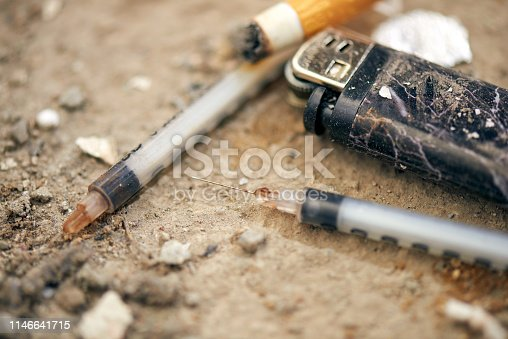 istock Used syringe on the ground - drugs Addiction equipment. 1146641715