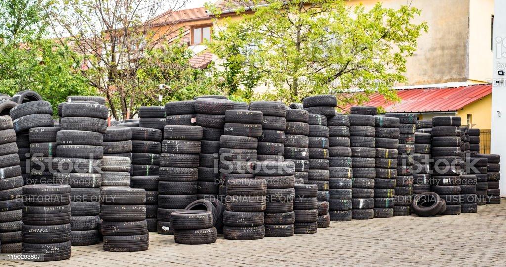 Pilas de neumáticos usados en el patio de vulcanización del taller - Foto de stock de Abandonado libre de derechos