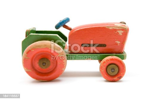 Run-down wooden toy tractor isolated on a white background.