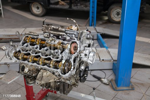 Used v8 engine mounted on a crane for installation on a car after a breakdown and renew in a vehicle repair workshop as a guarantee for the dealership. Auto service industry.