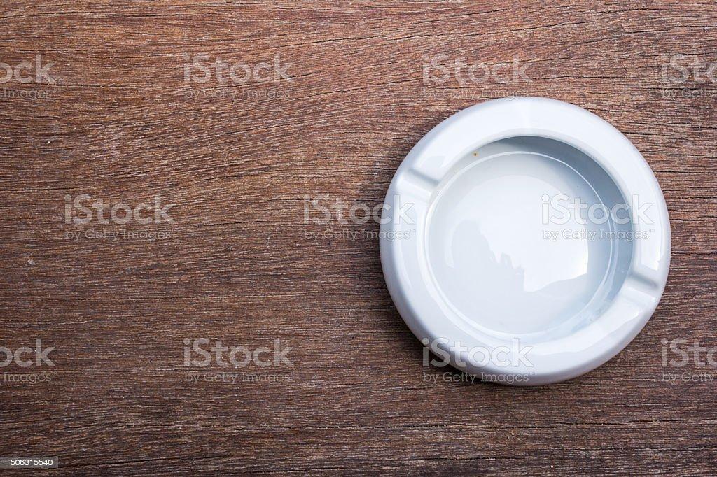 used white ashtray on wood table stock photo