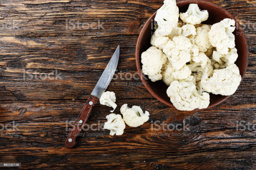 Useful cauliflower in a clay plate on a wooden table in the kitchen. top view stock photo