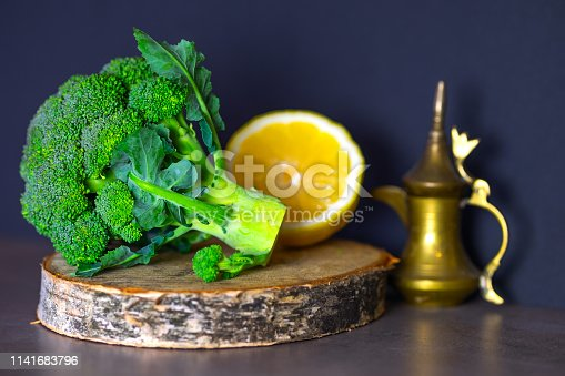 Useful foods are on the table, broccoli on a wooden stand and sliced lemon. The concept of healthy eating.