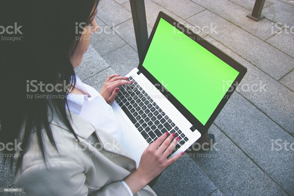 Useful gadget for business. Low angle closeup view of beautiful business woman in smart casual wear working on laptop while sitting outdoors. Green chroma key screen on laptop. royalty free stockfoto