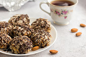 istock Useful homemade almond cake with coconut flakes on a light background and a cup of tea, copy space - Image 1179813386