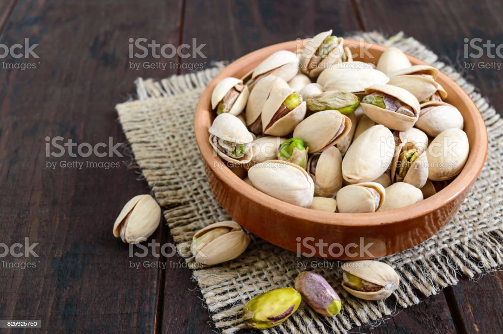 Useful nuts - pistachios in a ceramic bowl on a dark wooden background. stock photo