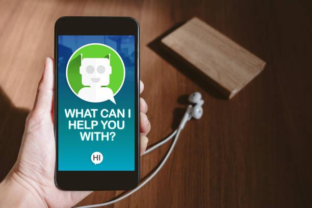 main de l'utilisateur détenant mobile bavardant avec chat bot sur l'écran du téléphone à blur table en bois, partager la vidéo sur le concept de médias sociaux, marketing stratégie numérique. - chatbot photos et images de collection