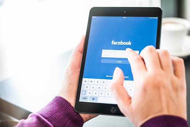 benutzer, die ein ipad mit facebook-homepage auf dem bildschirm - www kaffee oder tee stock-fotos und bilder