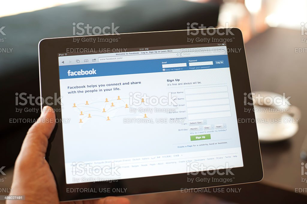 User holding an IPad with Facebook on screen stock photo