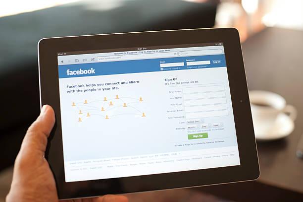 benutzer, die ein ipad mit facebook auf dem bildschirm - www kaffee oder tee stock-fotos und bilder