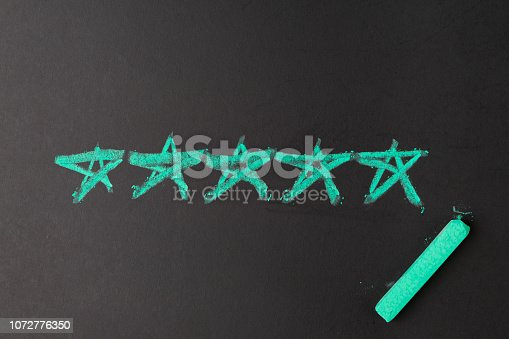 istock User reviews, customer feedback or UX User Experience concept, chalk drawing pastel green 5 stars on blackboard, feedback from real customer giving for great score on product and services 1072776350