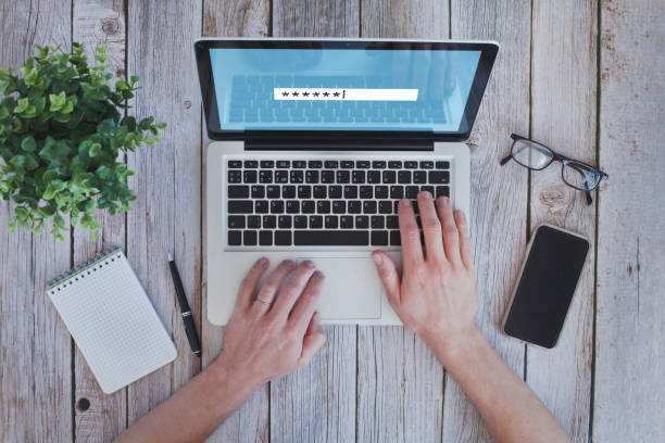 user typing password on computer, security code stock photo