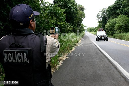 itabuna, bahia / brazil - february 28, 2012: Federal Highway Police Officer - PRF - is seen using a handheld radar device to control vehicle speed on the BR 101 Highway.