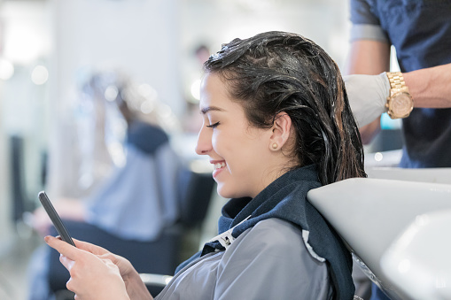 Uses Smart Phone While At Hair Salon Stock Photo Download Image Now Istock