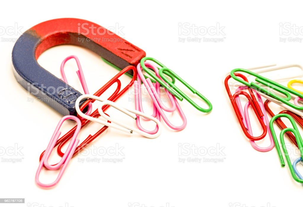 U-shaped red and blue magnet attracting paper clips isolated on white background stock photo