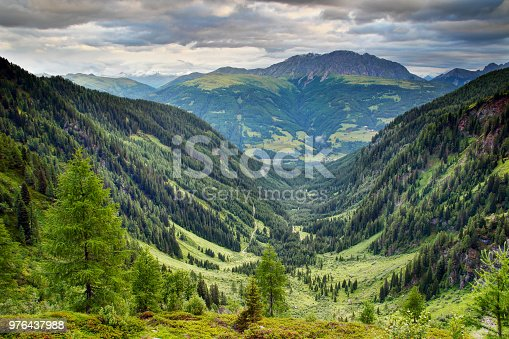 U-shaped valley with lush green forests and meadows in Karnische Alpen with Eggenkofel peak of Gailtaler Alpen Lienzer Dolomiten in cloudy morning, Untertilliach Lesachtal Osttirol Austria Europe