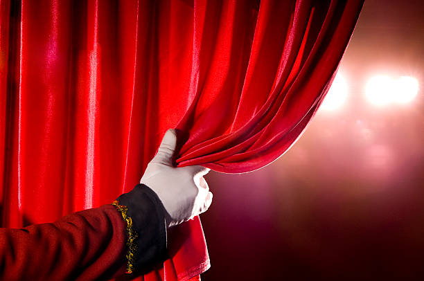 usher opening red theater curtain, with spotlights - curtain stock pictures, royalty-free photos & images