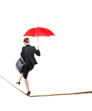 A Caucasian business woman carefully walking on a tightrope with a red umbrella. Business woman balancing work life and home life, navigating her career and future on a dangerous, risky and difficult path. She is walking away from the camera into the future. Photographed in studio on a white background.