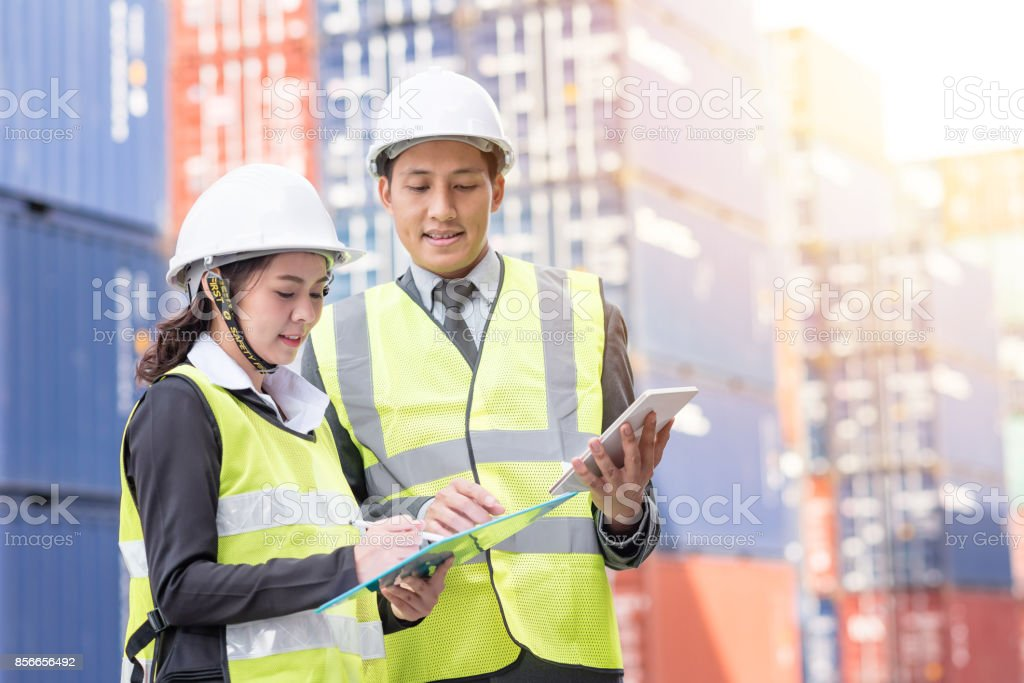 usinessman and secretary in logistic, export, import industry with shipping cargo container in background stock photo