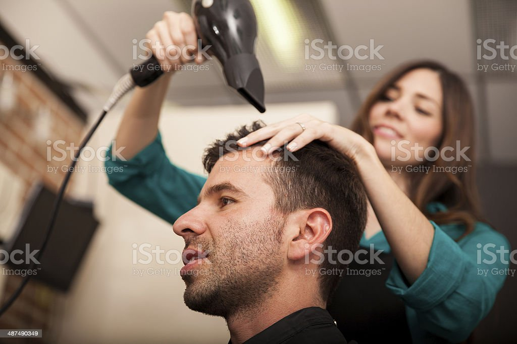 Using a blowdryer in a salon stock photo