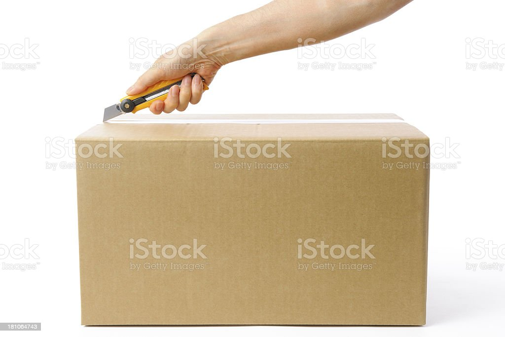 Using a box cutter to open a cardboard box stock photo