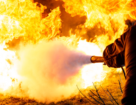 A man pointing a burst of carbon dioxide from a fire extinguisher towards the base of a fireball.