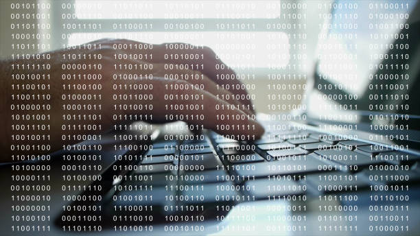 Using a computer overlaid with 8 bit binary code. stock photo
