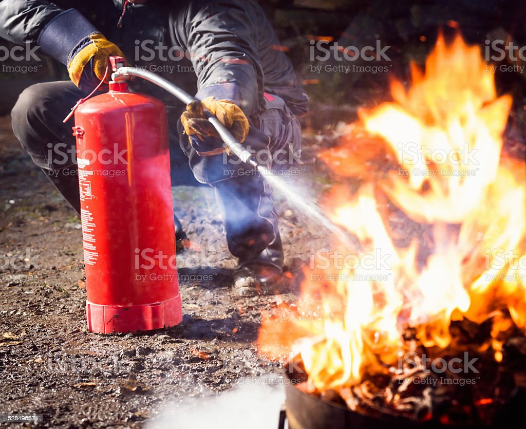 Using a fire extinguisher to fight fire stock photo