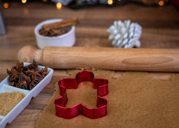 using a gingerbread man cookie cutter on gingerbread dough - christmas stock photos and pictures