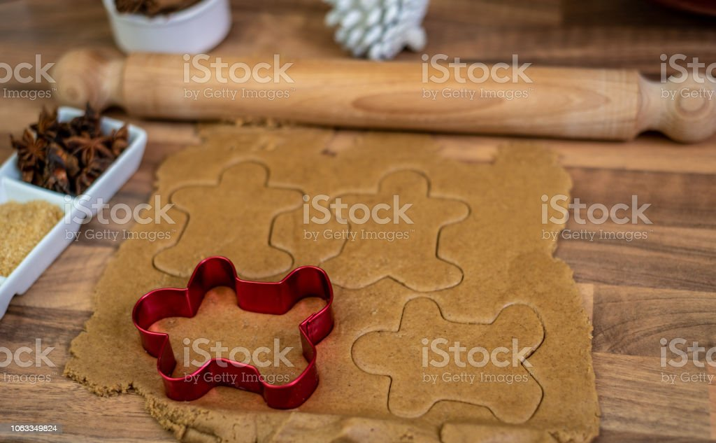 Using a gingerbread man cookie cutter on gingerbread dough stock photo