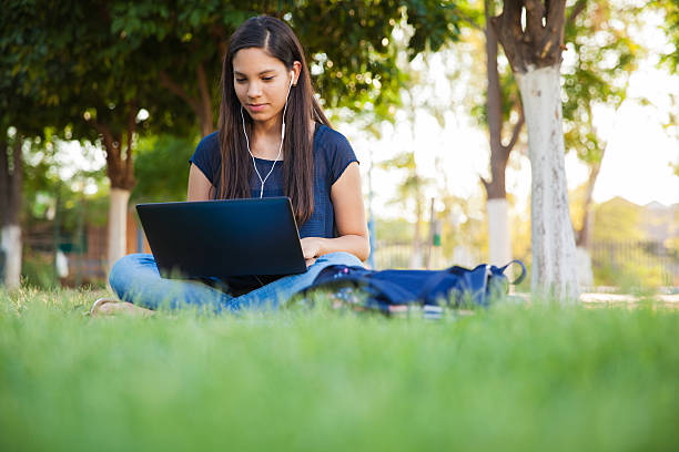 Using a laptop outdoors Beautiful teenage girl using a laptop and earbuds outdoors cute middle school girls stock pictures, royalty-free photos & images